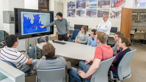 inside the Westerink civil engineering lab, with a student pointing to items on a screen as Professor Joannes Westerink (standing) and others look on